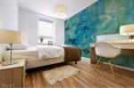 stampa murale adesiva astratta con tema che richiama un vortice marino con striature gialle applicato sulla parete di una camera da letto
