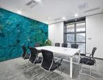murale astratto con trama grezza di colore blu che riproduce un effetto di pittura naturale con rilievi, linee spezzate e sfumature gialle applicato sulla parete di una sala riunioni