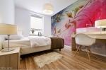 adesivo murale con tema astratto ispirato all'autunno con foglie stilizzate e dominante di colore rosa su parete di camera da letto
