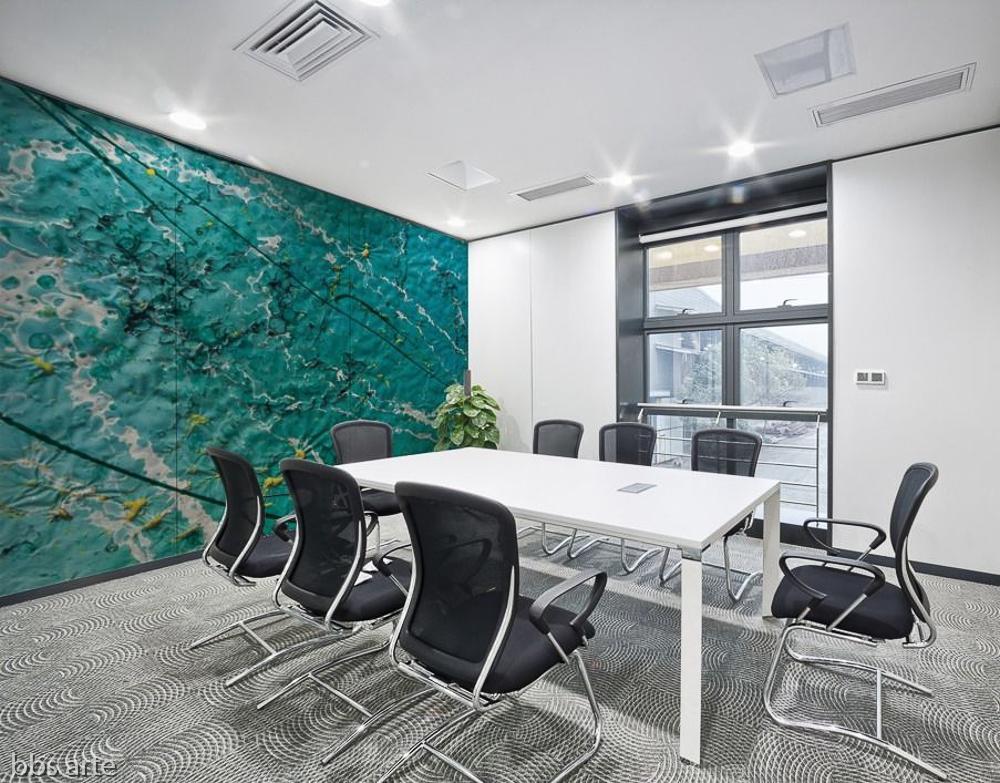 stampa murale astratta con striature di luci,linee,punti gialli e onde di colore verde chiaro e blu su parete di sala riunioni